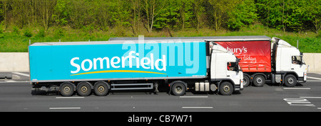 Supermarket food supply chain Somerfield articulated trailer & hgv lorry overtaking Sainsburys articulated trailer - Stock Photo
