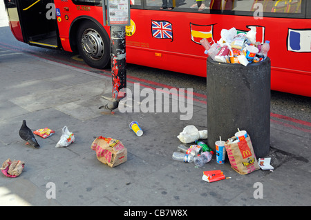 Waste management required to littering scene at street refuse bin full of rubbish garbage litter & trash spilling - Stock Photo