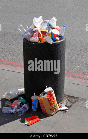Waste management required to overflowing roadside litter bin full with rubbish garbage litter & trash spilling on - Stock Photo