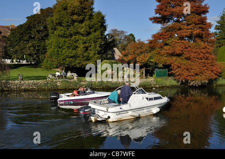Two motor boats cruise on the River Frome, past the grounds of the Priory Hotel, Wareham, Dorset. - Stock Photo