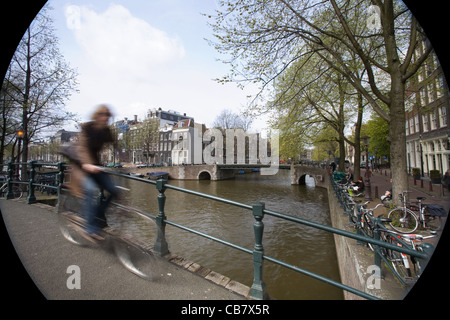Street scene, A bicycle crossing a bridge in an Amsterdam Channel, The Netherlands - Stock Photo
