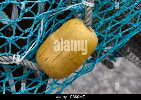 Fender on a shrimp cutter in the harbor of neuharlingersiel on the german north sea coast - Stock Photo