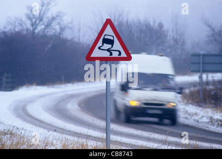 van travelling in winter snow passing warning sign of icy road near Leeds Yorkshire UK - Stock Photo