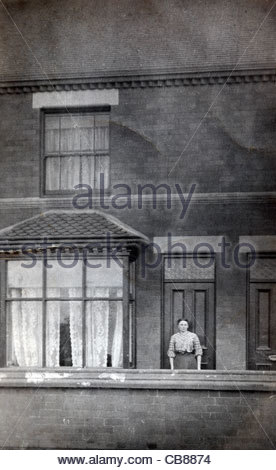 woman standing in front of the door of her house 1900s England - Stock Photo