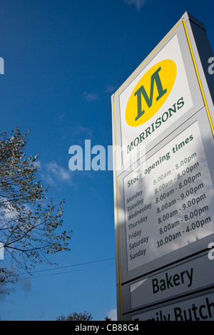 Morrison's supermarket sign showing opening times - Stock Photo
