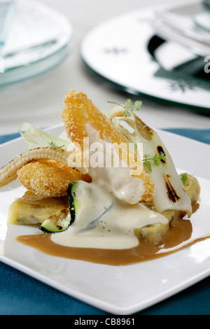Breaded Scampi over polenta with vegetables and seafood and cheese juice - Stock Photo