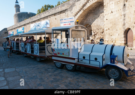A small road-train takes tourists on a trip around the walled town of Aigues-Mortes in the south of France. - Stock Photo
