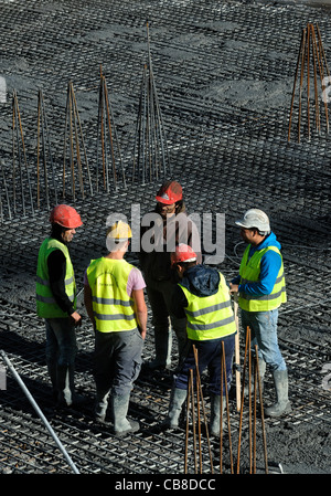 Construction workers chatting while on a break at a construction site - Stock Photo