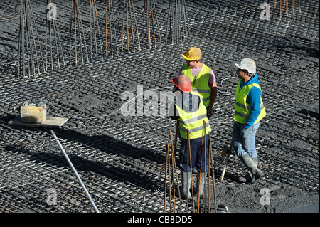 Construction workers chatting while taking a break at a construction site - Stock Photo