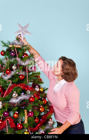 Photo of a woman at home decorating her Christmas tree and finishing off by putting the star on top. - Stock Photo