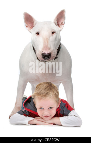 A little boy lying on the floor with his dog standing above him - Stock Photo