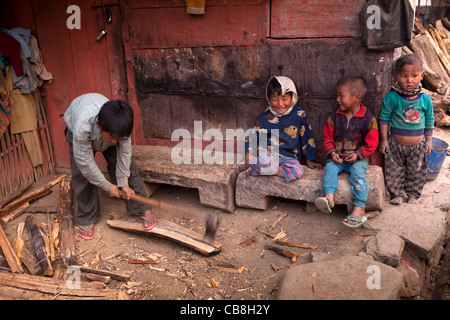 India, Nagaland, Jakhama Village, child chopping firewood with axe close to other young children - Stock Photo