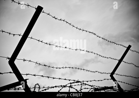 photo of old rusty barbed wire against sky - Stock Photo