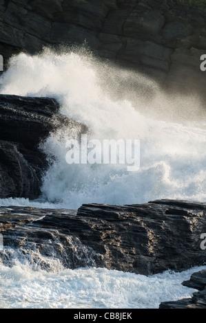 Waves crashing onto rocks at Trebarwith Strand beach on the northern coast of Cornwall in England - Stock Photo