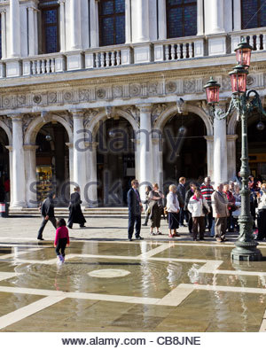St Marks Square, Venice Italy. Young girls plays in floodwater bubbling up from rain runoff drains. - Stock Photo