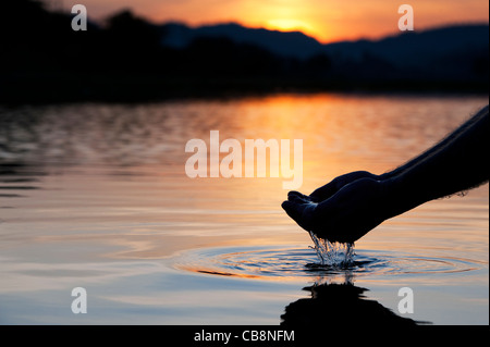 Cupped hands scooping up water in a still lake at sunrise in India. Silhouette - Stock Photo