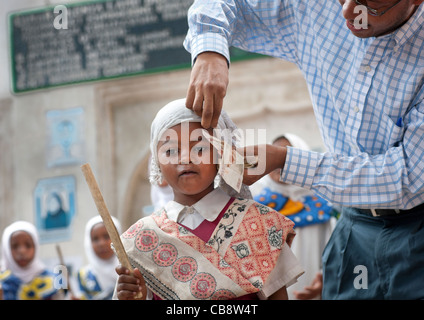 Man Putting Banknote Under Young Girl's Veil In Traditional Suit And Holding A Stick, Maulidi, Lamu, Kenya - Stock Photo