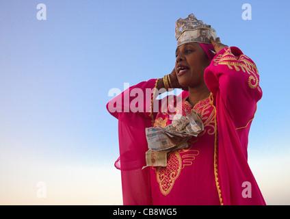 Woman Wearing Banknotes Arranging Herself During Maulidi Festival, Lamu, Kenya - Stock Photo
