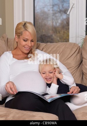 Happy pregnant mother and her three year old daughter reading a book together at home - Stock Photo