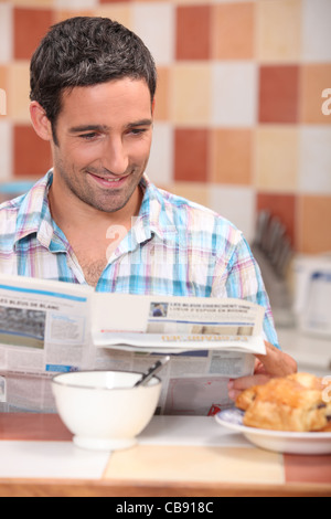 Man reading a journal over breakfast - Stock Photo