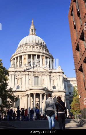 St.Pauls Cathedral in London on a clear sunny day with tourists flocking around to see the Occupy London protesters. - Stock Photo