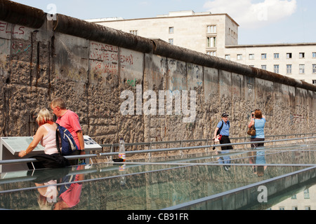 Sightseers at the Berlin Wall Monument - a preserved section of the Berlin Wall that formerly separated East from - Stock Photo