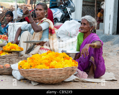 Indian women selling flowers for celebratory religious garlands at market in India - Stock Photo