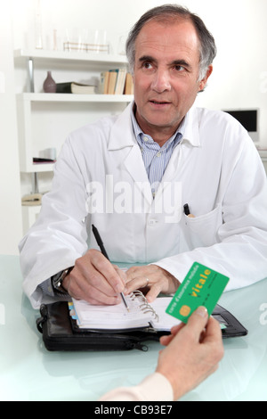 Woman giving a card to a doctor - Stock Photo