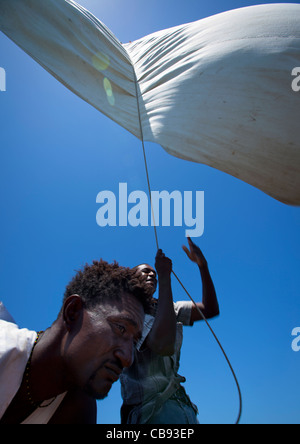 Man with rope during steerage of dhow, dhow race, Lamu, Kenya - Stock Photo