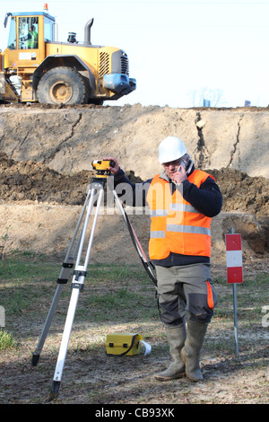 A mature engineer taking measures onsite. - Stock Photo