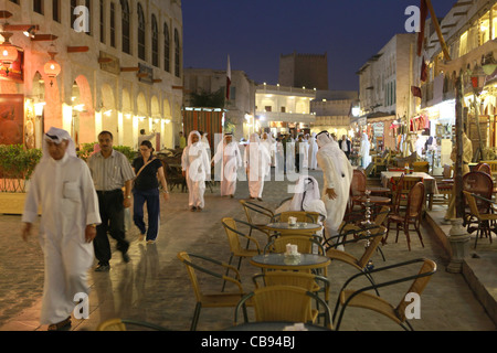 Qatari nationals and foreigners mingle in Souq Waqif in the evening - Stock Photo