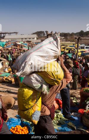India, Meghalaya, Jaintia Hills, Shillong district, Ummulong Bazar, man carrying three heavy sacks of produce - Stock Photo