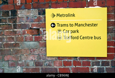 A yellow Metrolink sign on a brick wall at Stretford tram station in Manchester, England - Stock Photo