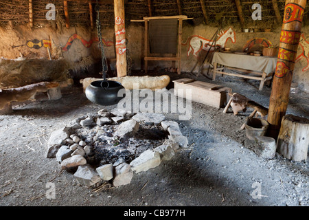 Interior of a replica neolithic thatched house with fireplace - Stock Photo
