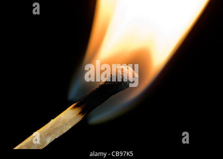 wooden matchstick igniting into flame against black background - Stock Photo