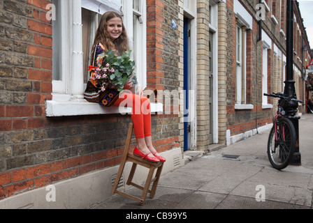 A girl sitting in a windowsill holding a bouquet, Columbia Market, London, UK - Stock Photo