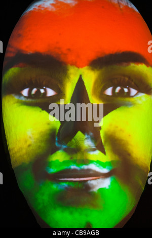 Huge sculpture of a face illuminated by an image of a Ghanaian flag painted face during the festival of lights 2011 - Stock Photo