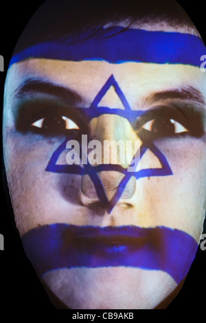 Huge sculpture of a face illuminated by an image of an Israeli flag painted face during the festival of lights 2011 - Stock Photo
