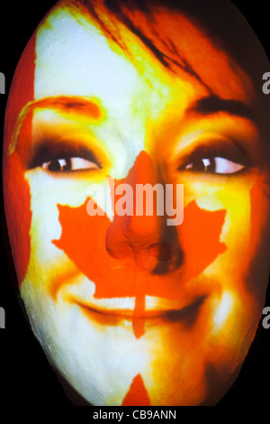 Huge sculpture of a face illuminated by an image of a Canadian flag painted face during the festival of lights 2011 - Stock Photo