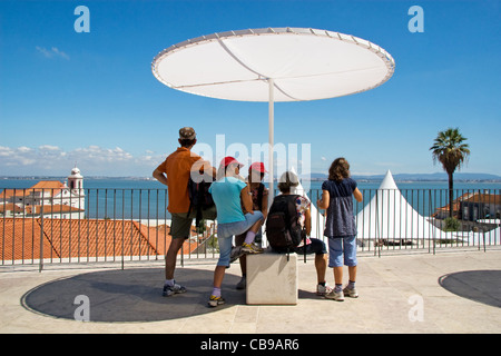 Family looking out over Alfama district and Tagus River. Miradouro de Santa Luzia, Lisbon, Portugal - Stock Photo