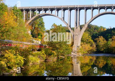Passenger cars of a train pass under a high bridge in a scenic area - Stock Photo