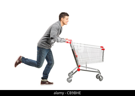Young man running and pushing an empty shopping cart - Stock Photo