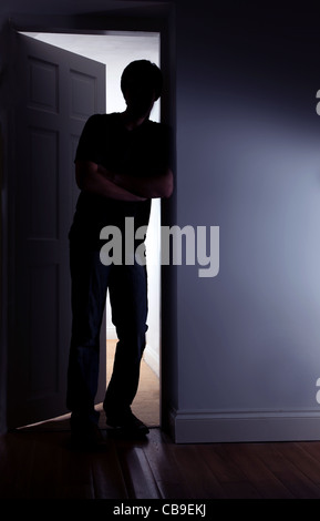 Young male standing leaning against an internal doorway. - Stock Photo