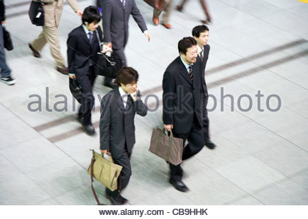 overhead view of group of young businessmen walking in one direction Japan Tokyo - Stock Photo