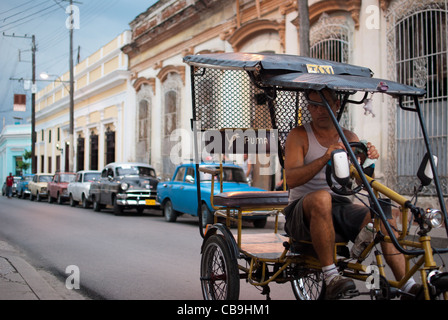 Bicycle rickshaw driver passing by, old American cars in the background - Stock Photo