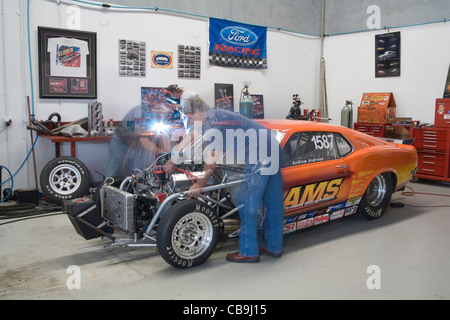Car enthusiasts working on a high powered V8 drag racing Ford Mutang car - Stock Photo