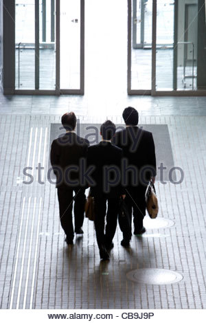 3 businessmen leaving an large office building - Stock Photo