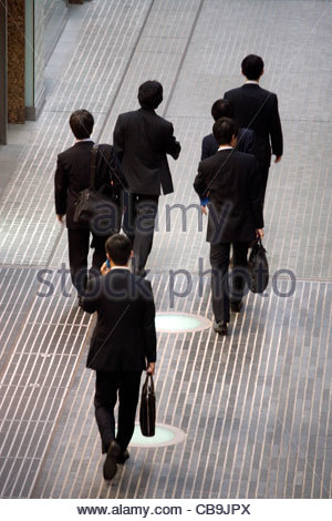 group of businessmen walking and talking - Stock Photo