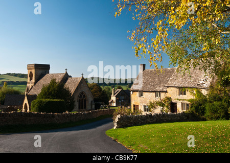 Cottages built of Cotswold stone beside St Barnabas church in the Cotswolds village of Snowshill with countryside - Stock Photo