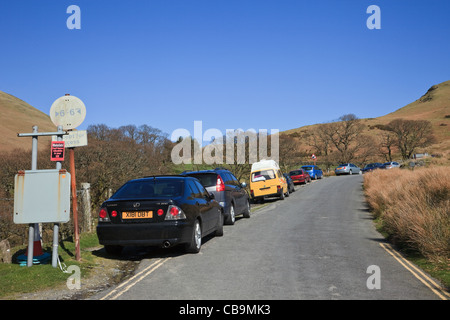 Cars parked on roadside along narrow Newlands Valley country road to avoid car parking fees in Lake District National - Stock Photo